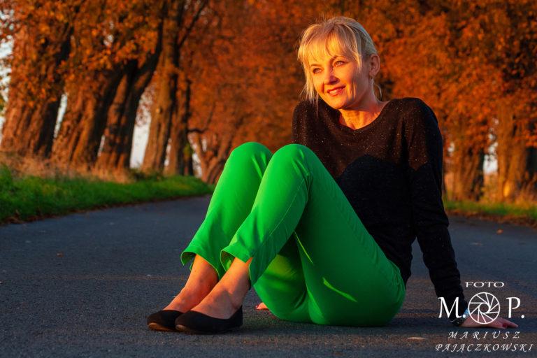 kobieta siedzi na drodze i patrzy na jesienny zachód słońca